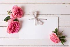 Rosas pasteis e Empty tag no fundo de madeira branco Imagem de Stock