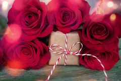 Rosas rojas con el regalo y el bokeh para el día de tarjetas del día de San Valentín Foto de archivo