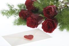 Rosas rojas con el sobre y el corazón Fotos de archivo libres de regalías