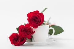 Rosas rojas con la taza de café de color blanco en un fondo blanco Fotos de archivo libres de regalías
