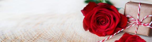 Rosas rojas con un regalo en la madera rústica brillante Imágenes de archivo libres de regalías