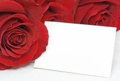Rosas rojas con una nota en blanco Imagen de archivo libre de regalías