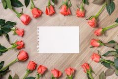 Rosas rojas con una nota en blanco Foto de archivo