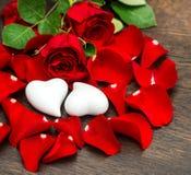 Rosas rojas de la decoración del día de tarjetas del día de San Valentín y dos corazones Imagen de archivo