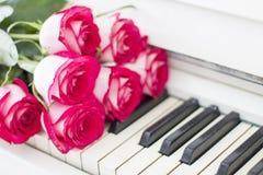 Rosas rojas de lujo en un piano Ramo de rosas rojas y de piano Imagenes de archivo