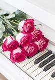Rosas rojas de lujo en un piano Ramo de rosas rojas y de piano Foto de archivo libre de regalías