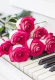 Rosas rojas de lujo en un piano Ramo de rosas rojas y de piano Foto de archivo
