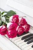 Rosas rojas de lujo en un piano Ramo de rosas rojas y de piano Fotos de archivo