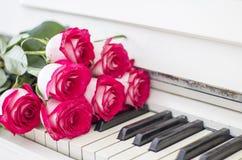 Rosas rojas de lujo en un piano Ramo de rosas rojas y de piano Fotografía de archivo libre de regalías