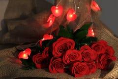 Rosas rojas del ramo con el rojo oído para el día de tarjetas del día de San Valentín Fotos de archivo