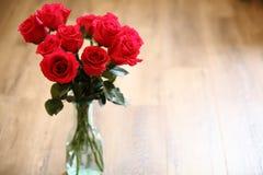 Rosas rojas en el florero de cristal con el fondo de madera Copie el espacio Fotografía de archivo