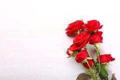 Rosas rojas en el fondo de madera blanco Fotos de archivo libres de regalías