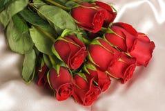 Rosas rojas en el satén amarillento foto de archivo libre de regalías
