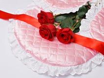 Rosas rojas en el satén rosado Fotografía de archivo