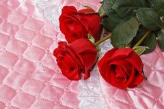 Rosas rojas en el satén rosado Imágenes de archivo libres de regalías