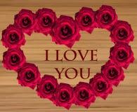 Rosas rojas en la forma de un coraz?n en fondo de madera imagen de archivo