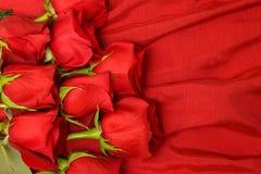 Rosas rojas en la seda Fotos de archivo
