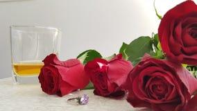 Rosas rojas en la tabla blanca cerca del anillo de plata con el cristal violeta grande foto de archivo