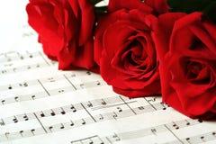 Rosas rojas en música de hoja Imagen de archivo