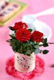 Rosas rojas en un florero blanco en fondo rosado Foto de archivo