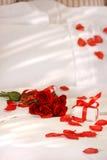 Rosas rojas en una cama Imágenes de archivo libres de regalías