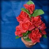 Rosas rojas hechas de tela en un florero en un paño azul Imagenes de archivo