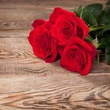 Rosas rojas hermosas en el viejo tablero foto de archivo libre de regalías