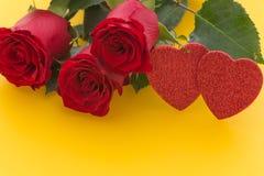 Rosas rojas hermosas ocasionales en el fondo amarillo con el lugar para los esmeros o los deseos fotografía de archivo
