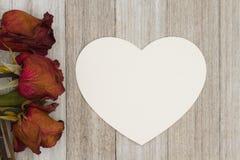 Rosas rojas muertas con la tarjeta de la corazón-forma en backgroun de madera resistido Imagenes de archivo