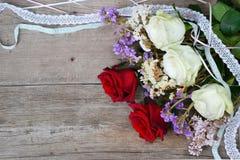 Rosas rojas y blancas y cordones en fondo de madera Foto de archivo