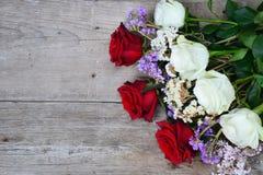 Rosas rojas y blancas en fondo de madera Fotografía de archivo libre de regalías