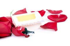 Rosas rojas y caramelo con un carte cadeaux en blanco Foto de archivo libre de regalías