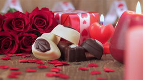 Rosas rojas y caramelos de chocolate con las velas en la madera almacen de video