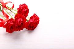 Rosas rojas y cinta en la tabla Imagen de archivo libre de regalías