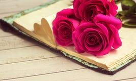 Rosas rojas y el libro viejo en una tabla de madera blanca en estilo del vintage Día romántico del ` s de la tarjeta del día de S Foto de archivo libre de regalías