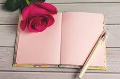 Rosas rojas y el libro viejo en una tabla de madera en estilo del vintage Día romántico del ` s de la tarjeta del día de San Vale Imagen de archivo