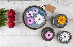 Rosas rojas y flores del gerbera en la tabla de madera Fotografía de archivo libre de regalías