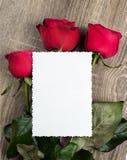 Rosas rojas y hoja en blanco en de madera Imagen de archivo libre de regalías