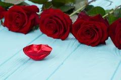 Rosas rojas y labios rojos del caramelo imágenes de archivo libres de regalías