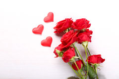 Rosas rojas y pequeños corazones en fondo de madera Fotos de archivo