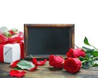 Rosas rojas y regalo para el día o un cumpleaños de la tarjeta del día de San Valentín Fotografía de archivo