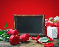 Rosas rojas y regalo para el día o un cumpleaños de la tarjeta del día de San Valentín Imagen de archivo