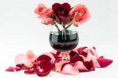Rosas rojas y rosadas en el vidrio de vino Foto de archivo libre de regalías