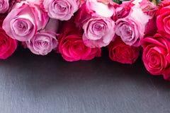 Rosas rojas y rosadas en la tabla Fotos de archivo libres de regalías