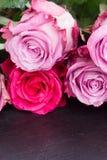Rosas rojas y rosadas en la tabla Imágenes de archivo libres de regalías