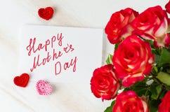 Rosas rojas y tarjeta con día de madres feliz del texto Foto de archivo libre de regalías