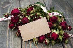 Rosas rojas y tarjeta de felicitación Fotografía de archivo
