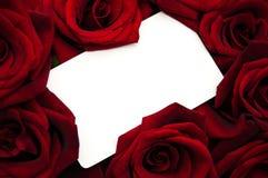 Rosas rojas y tarjeta de felicitación Fotos de archivo