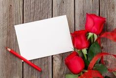Rosas rojas y tarjeta de felicitación Imagen de archivo