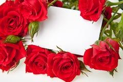 Rosas rojas y tarjeta en blanco de la invitación Foto de archivo